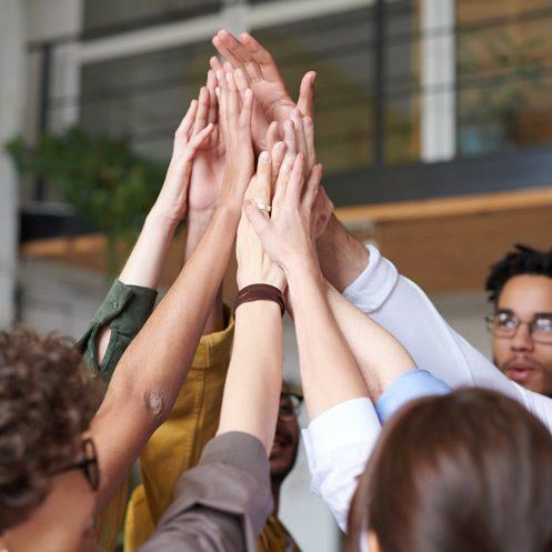 Equipo de profesionales chocando sus manos en las oficina
